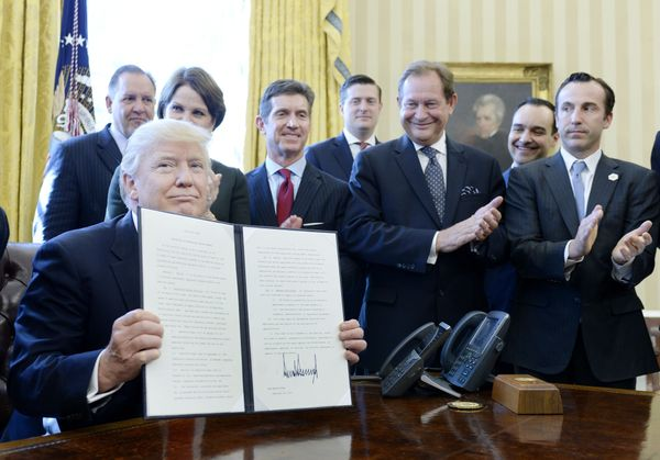 Trump, flanked by business leaders, signs an executive order establishing regulatory reform officers and task forces in U.S.