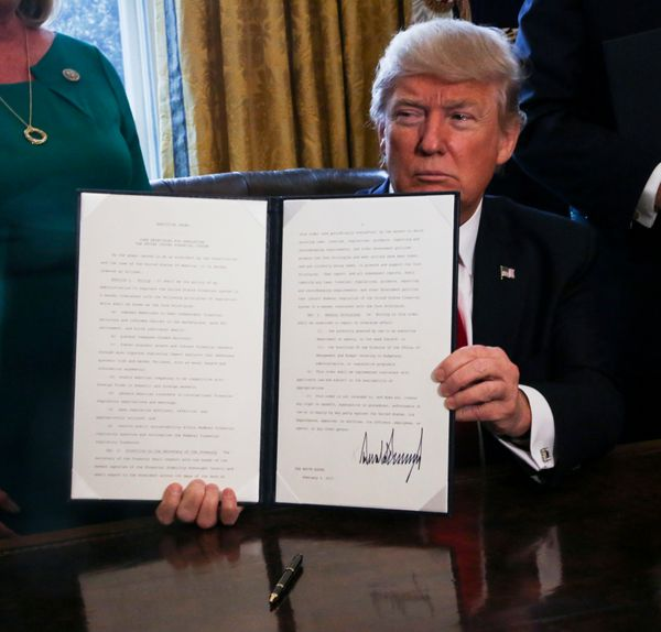 Trump signs executive orders, including one to roll back financial regulations of the Obama era, on Feb. 3, 2017.