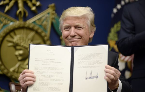 Trump holds up signed executive orders in the Hall of Heroes at the Department of Defense in Arlington, Virginia, on Jan