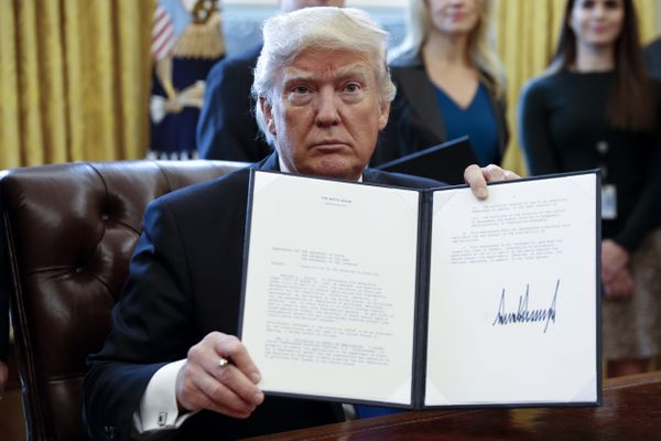 Trump displays one of five executive orders he signed related to the oil pipeline industry for a photograph in the Oval Offic