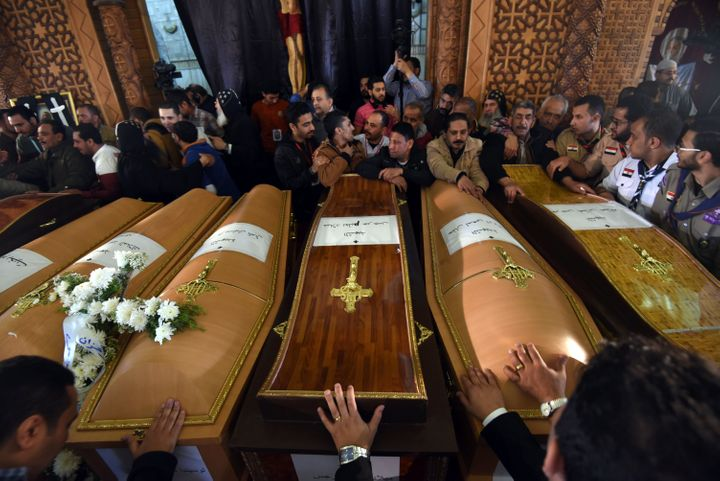 Mourners pray next to coffins of the victims of the blast at the Coptic Christian Saint Mark's church in Alexandria the previ