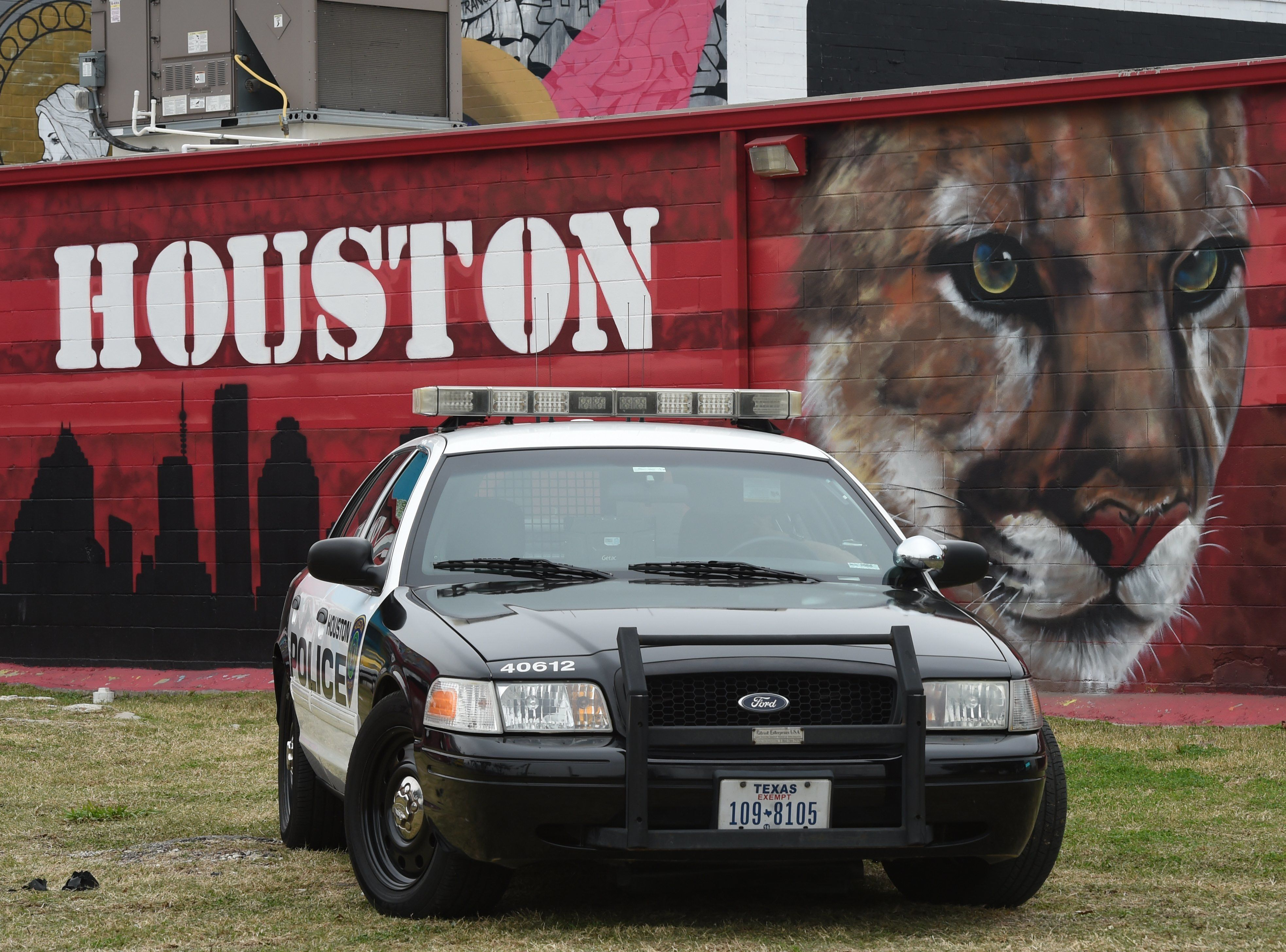 A Houston police car in front of a graffiti-covered building in the Old Chinatown section of downtown near the  NFL Experience  at the George R. Brown Convention Center February 4, 2017 in Houston, Texas one day before the New England Patriots play the Atlanta Falcons in Super Bowl 51. / AFP / TIMOTHY A. CLARY        (Photo credit should read TIMOTHY A. CLARY/AFP/Getty Images)