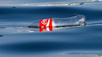 Paracas, Peru - January 20, 2015: Human pollution in the Pacific Ocean currents. An empty plastic coke bottle floats on the surface