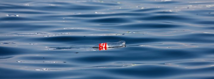 A Coke bottle floats in the Pacific Ocean.