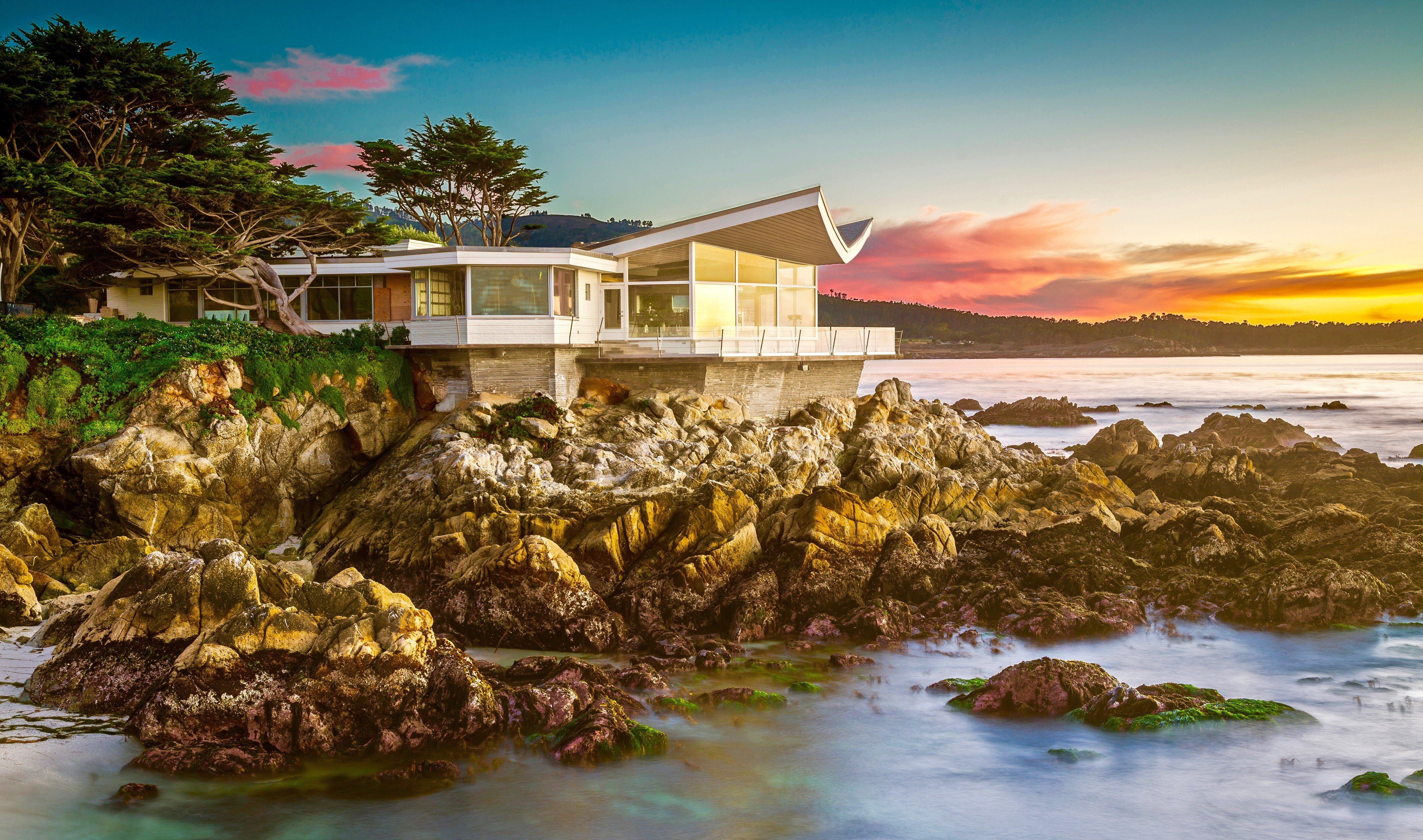The Butterfly House sits on the rocks as the Pacific ocean waves crash on the rocky beach coast in Carmel California.