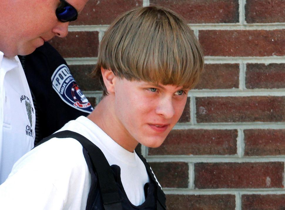 "Dylann Roof, who killed nine people in a South Carolina church, is led into a courthouse on June 18, 2015. ""T"