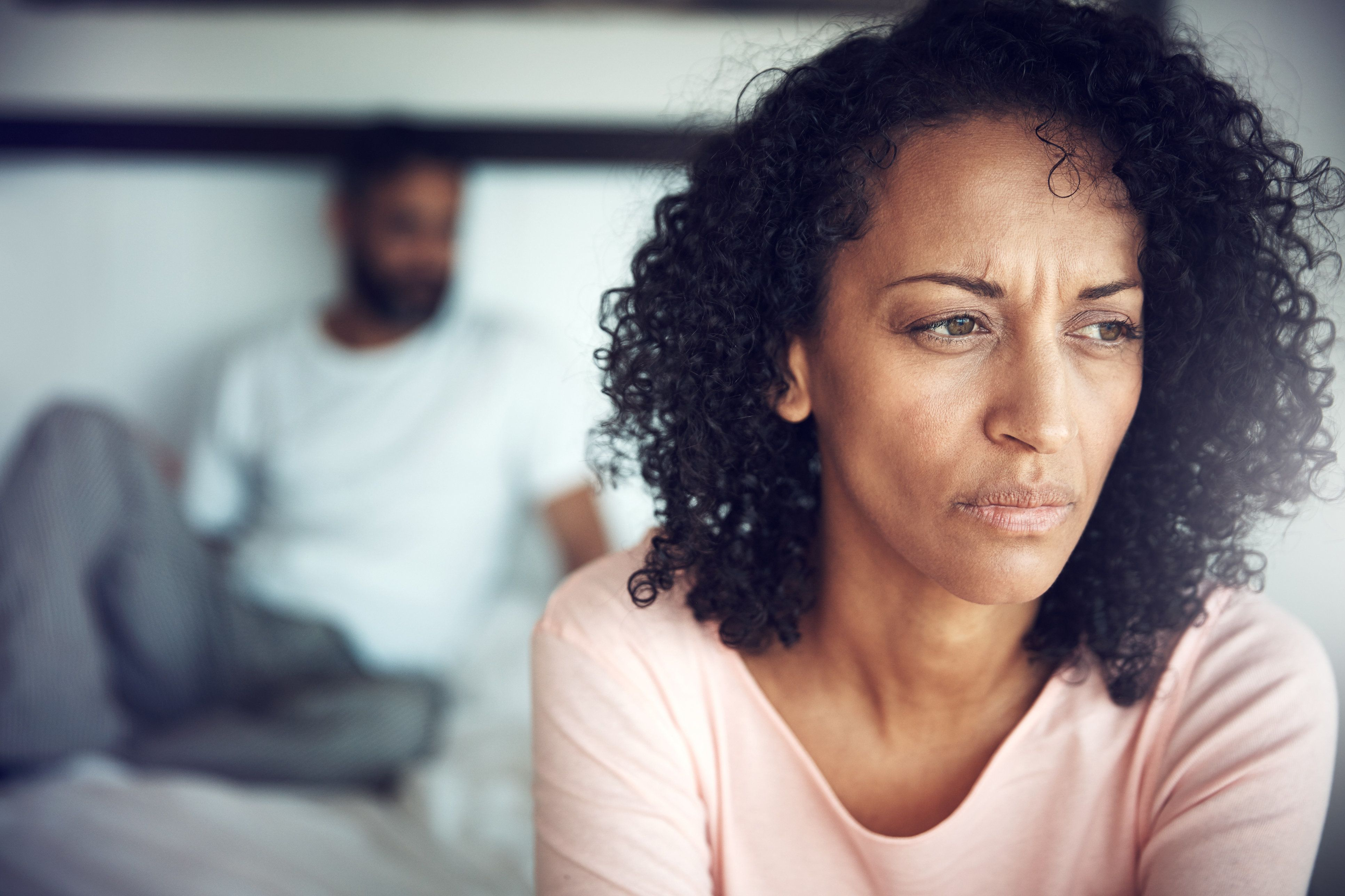 Shot of a mature woman looking upset with her husband in the background