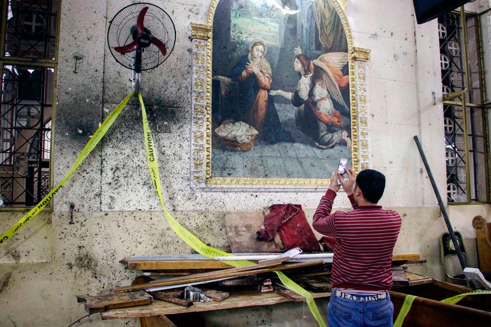 An Egyptian man uses his cell phone to take pictures of the destruction, debris, and bloodstains on the walls and icon murals