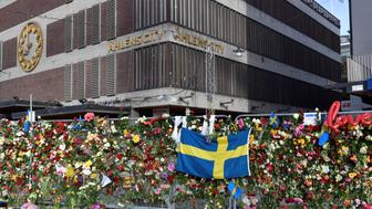 Flowers are seen on a fence by Ahlens department store following Friday's attack in central Stockholm, Sweden, April 9, 2017. According to local media, the flowers were moved to the steps at Sergels Torg on Sunday morning.    TT News Agency/Jonas Ekstromer/via REUTERSATTENTION EDITORS - THIS IMAGE WAS PROVIDED BY A THIRD PARTY. FOR EDITORIAL USE ONLY. SWEDEN OUT. NO COMMERCIAL SALES.