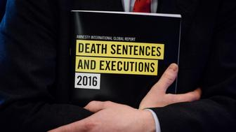 In this photo taken on April 10, 2017, a global report booklet by Amnesty International entitled 'Death Sentence and Execution' is held by James Lynch, deputy director of the Global Issues Programme at Amnesty International, after a media briefing at the Foreign Correspondents' Club (FCC) in Hong Kong.  China executed more people in 2016 than all other nations combined, Amnesty International said on April 11, 2017, as death penalties in the world decreased overall.  / AFP PHOTO / ANTHONY WALLACE        (Photo credit should read ANTHONY WALLACE/AFP/Getty Images)