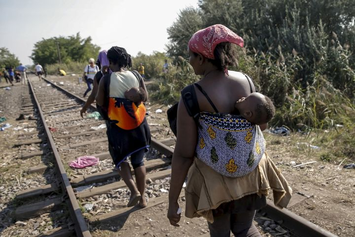 Migrants, hoping to cross into Hungary, walk with babies on their backs along a railway track outside the village of Horgos i