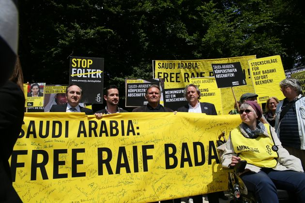 Amnesty International activists held a protest demanding the release of blogger Raif Badawi and to stop...