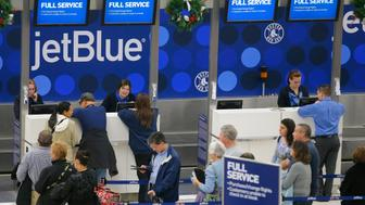 Passengers wait in line at the JetBlue ticket counter at Logan International Airport in Boston, Massachusetts January 6, 2014.   After five days of scrambling to catch up from storm delays, JetBlue said it would halt operations at New York's three area airports and Boston Logan International Airport from 5 p.m. ET (2200 GMT) Monday until 10 a.m. ET (1500 GMT) on Tuesday to give crews time to rest. REUTERS/Brian Snyder (UNITED STATES - Tags: ENVIRONMENT TRANSPORT BUSINESS EMPLOYMENT)