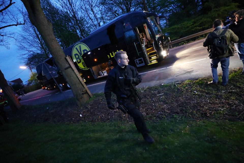 Police with the Borussia Dortmund team bus after an explosion near their hotel before the game.