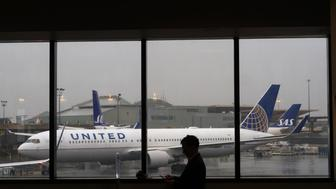 NEWARK, NJ - APRIL 6: A man uses his mobile phone in front of a United Airlines plane at Newark Liberty Airport during a storm on April 6, 2017, in Newark NJ. (Photo by Gary Hershorn/Getty Images)