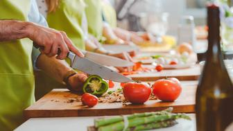 Group of people waering aprons taking part in cooking class, preparing food, slicing vegetables. Close up of hands, unrecognizable people.