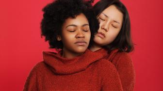 Asian and Black woman hugging with their eyes closed and wearing red jumpers, shot in front of red background.