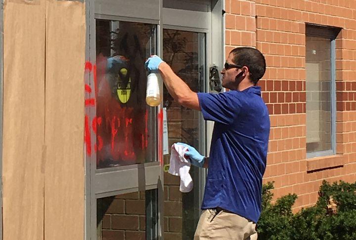 A man scrubs anti-Semitic graffiti from the Jewish Community Center of Northern Virginia in Fairfax, Virginia, on April 11, 2017.
