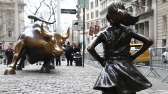 NEW YORK, USA - MARCH 29: The 'Fearless Girl' statue, a four-foot statue of a young girl, defiantly looks up the iconic Wall Street 'Charging Bull' sculpture in New York City, United States on March 29, 2017.  'Fearless Girl' statue was installed in front of the bronze 'Charging Bull' for International Women's Day earlier this month to draw attention to the gender pay gap and lack of gender diversity on corporate boards in the financial sector. The statue will remain at her post until February 2018.        (Photo by Volkan Furuncu/Anadolu Agency/Getty Images)