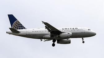 CHICAGO, USA - APRIL 11: A passenger plane of United Airlines flies over Chicago, United States on April 11, 2017. Passengers, who couldn't be convinced to fly next flight, are dropped off with police officers after United Airlines' overbook application sold a ticket to two people. CEO of United Airlines Oscar Munoz said that the incident was upsetting. (Photo by Bilgin S. Sasmaz/Anadolu Agency/Getty Images)