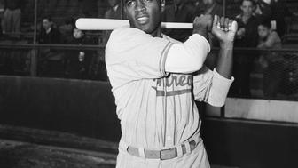 (Original Caption) 4/10/1947-New York, NY-Jackie Robinson, first Negro to be signed up by a Major League baseball team, is shown in post-swing position in front of the stands. Robinson changed uniforms after playing with Montreal in an exhibition game against the Dodgers.