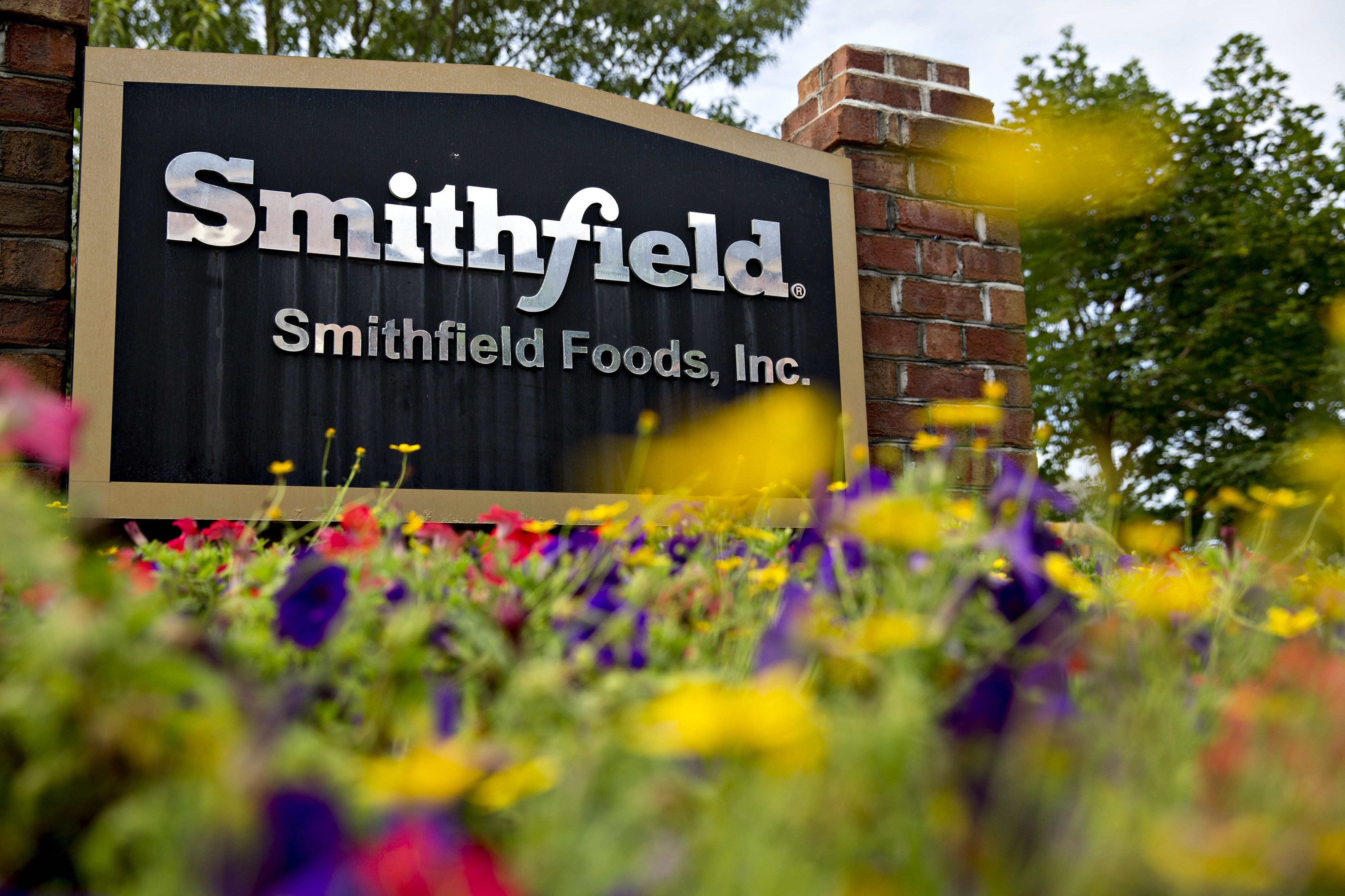 Signage stands outside of Shuanghui International Holdings Ltd.'s Smithfield Foods Inc. headquarters in Smithfield, Virginia, U.S., on Tuesday, June 28, 2016. When Chinese suitors took over Smithfield Foods it sent tremors through the tiny town that calls itself the Ham Capital of the World. Three years on, residents and union leaders say the initial fears about the buyer from a Communist-ruled nation proved unfounded. Photographer: Andrew Harrer/Bloomberg via Getty Images