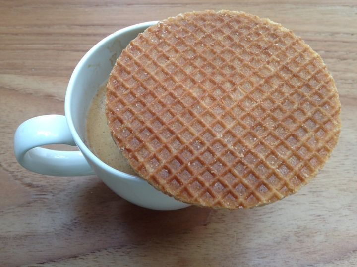 A stroopwafel served on top of a coffee.