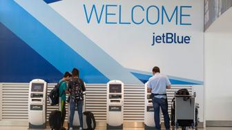Travelers check in at JetBlue Airways Corp.'s Terminal 5 at John F. Kennedy International Airport (JFK) airport in New York, U.S., on Friday, Aug. 7, 2015. The largest airline at JFK by passengers, JetBlue will be building a 505-room, $250 million TWA Flight Center Hotel, scheduled for completion in 2018. Photographer: Michael Nagle/Bloomberg via Getty Images