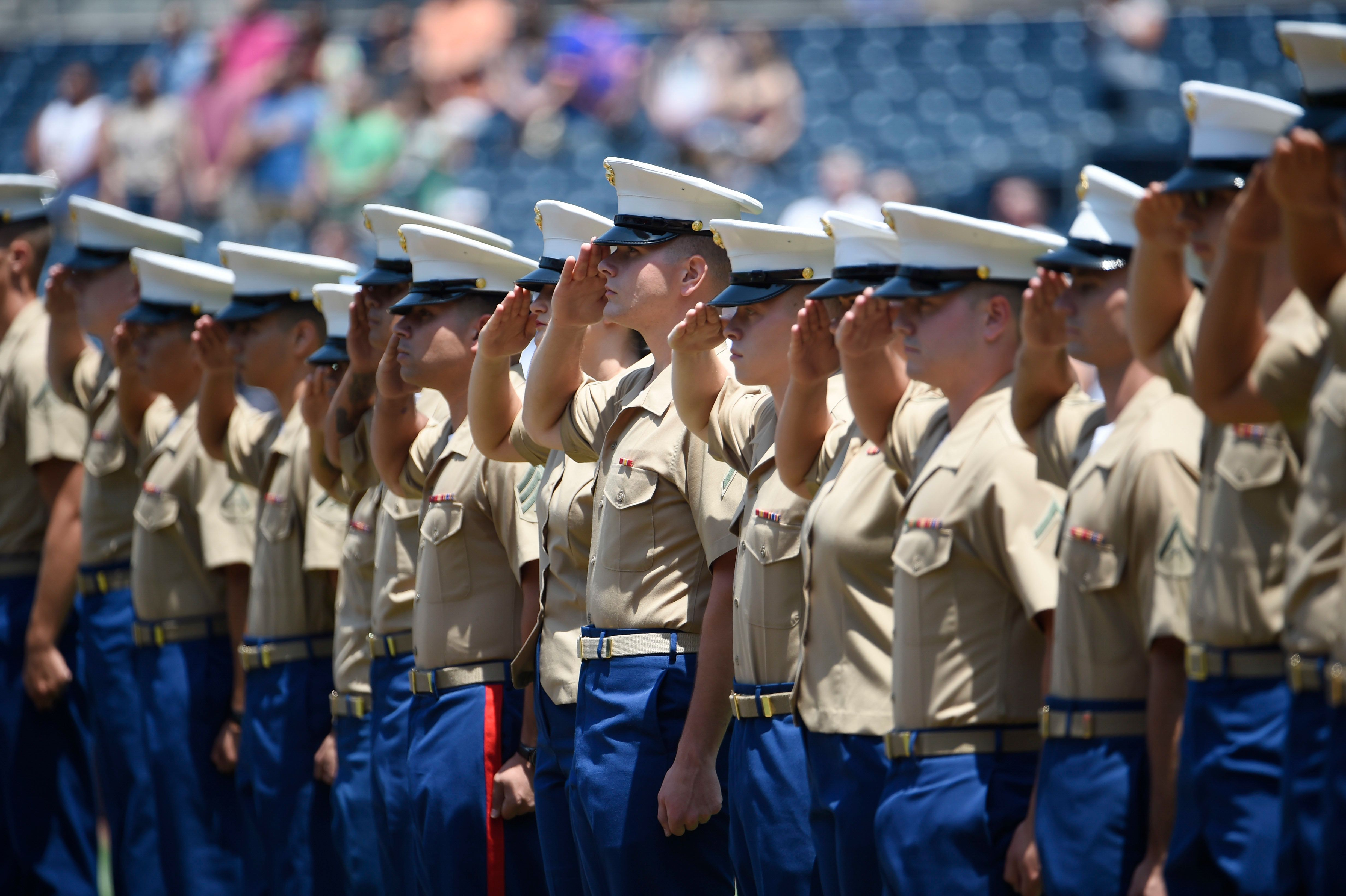 U.S. Marines salute during the national anthem before a baseball game between the San Diego Padres and the Cincinnati Reds on