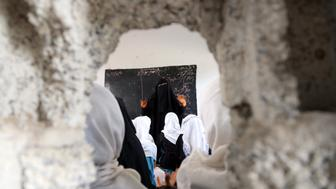 TOPSHOT - Yemeni students study in a classroom in the Yemeni port city of Hodeidah, on March 15, 2016, which was damaged in the country's ongoing conflict between the Saudi-led Arab coalition fighting Shiite Huthi rebels. The conflict in Yemen, which escalated with the intervention of the Saudi-led coalition two years ago, has more than doubled the number of children deprived of schooling to some 3.5 million, threatening the future of a whole generation in the impoverished country. / AFP PHOTO / STRINGER / TO GO WITH AFP STORY BY JAMIL NASSER        (Photo credit should read STRINGER/AFP/Getty Images)