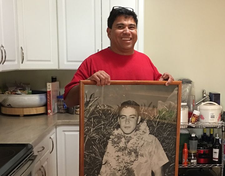 <em>Standing in the middle of his spotless kitchen, Freitas holds up a large photo of his father from his youth. </em>