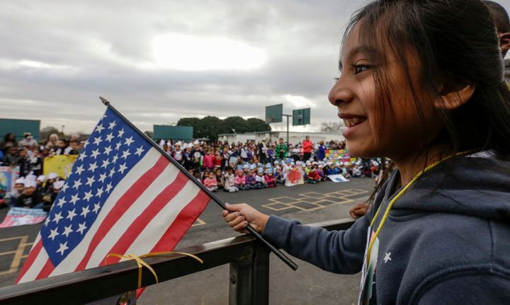 Alexandra Rojas, a 5th grader, holds a flag at an annual Stepping Out for Peace March held by students to mark Martin Lu