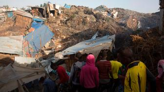 TOPSHOT - People look at the damage done to dwellings built near the main landfill of Addis Ababa on the outskirts of the city on March 12, 2017, after a landslide left at least 30 people dead. At least 30 people died and dozens more were hurt in a giant landslide at Ethiopia's largest rubbish dump outside Addis Ababa, a tragedy squatters living there blamed on a biogas plant being built nearby. The landslide late on March 11 saw dozens of homes of people living in the dump levelled after a part of the largest pile of rubbish at the Koshe landfill collapsed, an AFP journalist said.  / AFP PHOTO / ZACHARIAS ABUBEKER        (Photo credit should read ZACHARIAS ABUBEKER/AFP/Getty Images)