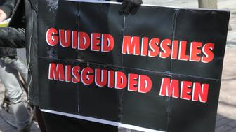 Demonstrator holds a sign saying 'Guided Missiles, Misguided Men' during a protest against US President Donald Trump's decision to launch airstrikes against Syria on April 8, 2017 in Toronto, Ontario Canada. Protestors gathered to outside the American Consulate in Toronto to denounce this week's airstrikes against the Syrian regime. America launched a missile strike against Syria for the first time since the civil war began, targeting an airbase in the small town of Idlib from which the United States claims this weeks chemical weapons attack on civilians was launched by Bashar al-Assads regime. (Photo by Creative Touch Imaging Ltd./NurPhoto via Getty Images)