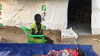 A young girl in Ganyiels health clinic watches her 3-year-old sister who is sick with cholera Her mother brought her over from Tayar island to seek treatment in the clinic