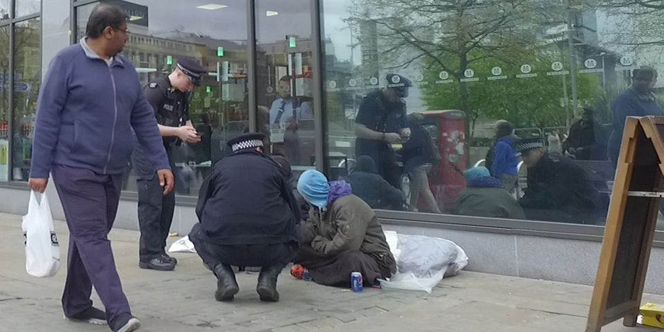 Two police officers check the wellbeing of a homeless man near Piccadilly Gardens in Manchester this