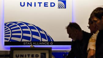 Passengers use self check-in kiosks inside the United Continental Holdings Inc. terminal at Newark Liberty International Airport (EWR) in Newark, New Jersey, U.S., on Wednesday, April  12, 2017. United Airlines is under fire for forcibly removing a passenger from a plane in Chicago shortly before departure to make room for company employees, an incident which demonstrates how airline bumping can quickly veer into confrontation. Photographer: Timothy Fadek/Bloomberg via Getty Images