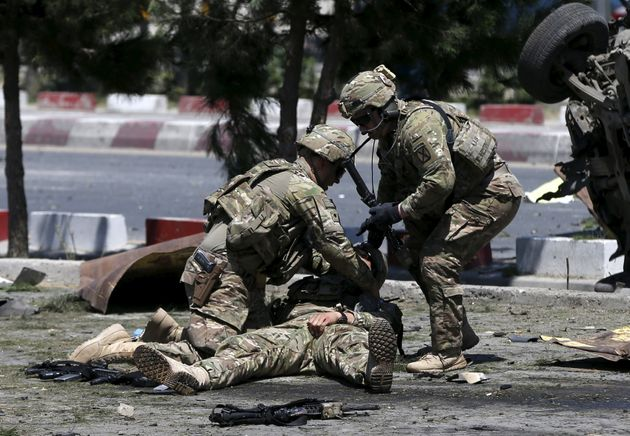 U.S. troops attend to a wounded American soldier after a bomb blast in Kabul, Afghanistan, in June