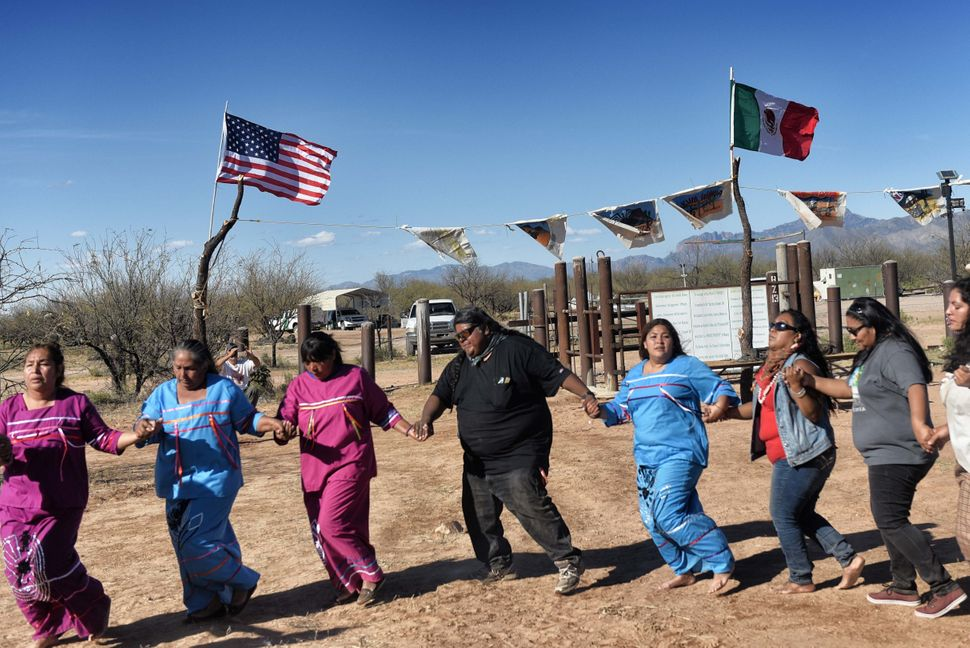 Indigenous people from the Tohono O'odham ethnic group dance and sing to protest against President Donald Trump's intention t