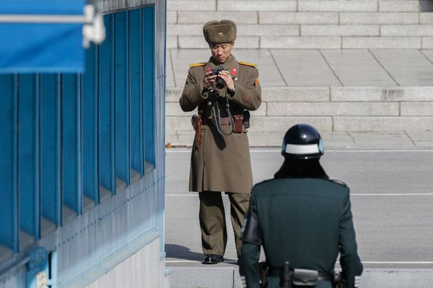 A North Korean solider and a South Korean soldier stand guard at the demilitarized