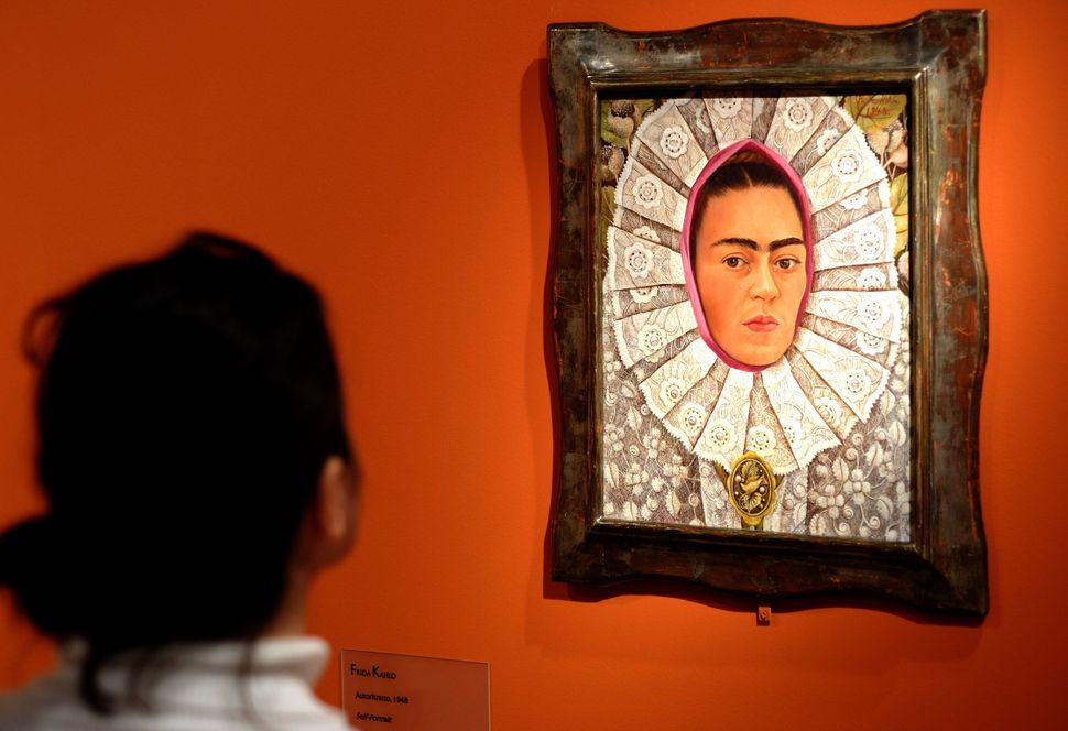 "A visitor looks at ""Self-Portrait"" by Frida Kahlo during an exhibition in Rome."