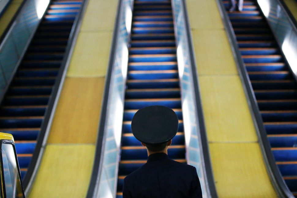 A railway worker stands in front of escalators at a subway station visited by foreign reporters in central Pyongyang, April 1