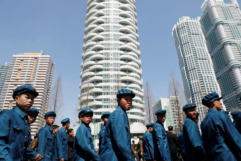 Men in uniforms walk between buildings after the opening ceremony of a newly constructed residential complex in Pyongyang, Ap