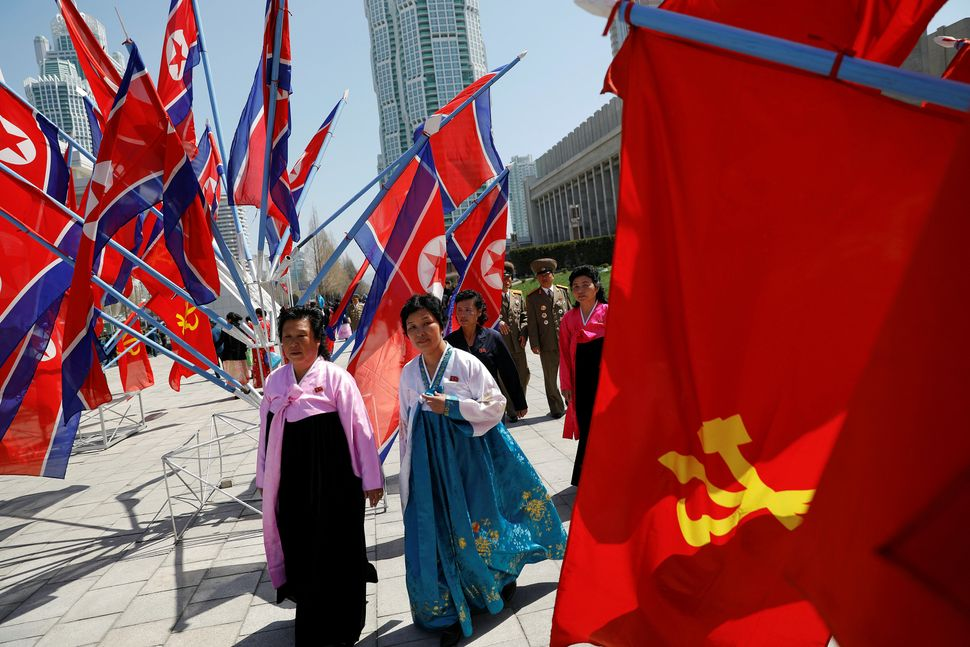Women wearing traditional dresses walk through a newly constructed residential complex after its opening ceremony in Pyongyan