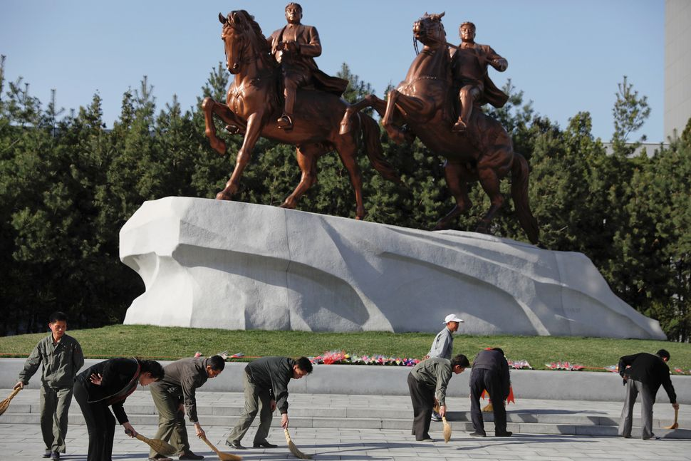People sweep in front of statues of former North Korean leaders Kim Il Sung and Kim Jong Il in central Pyongyang, April 12, 2