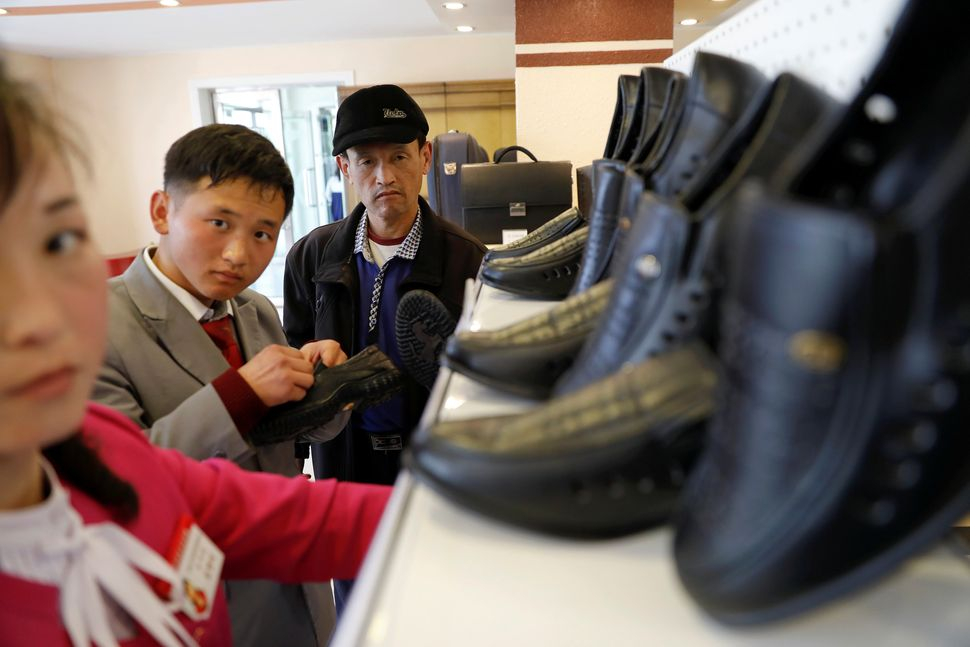 People check shoes in a shop in a newly constructed residential complex after its opening ceremony in Pyongyang, April 13, 20
