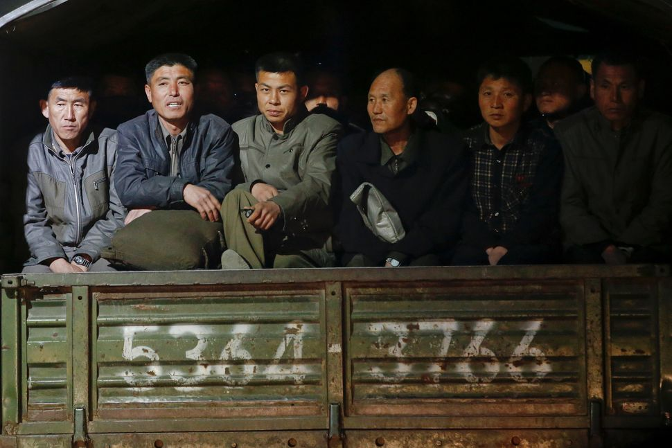 Men ride at the back of a truck in central Pyongyang, April 11, 2017.