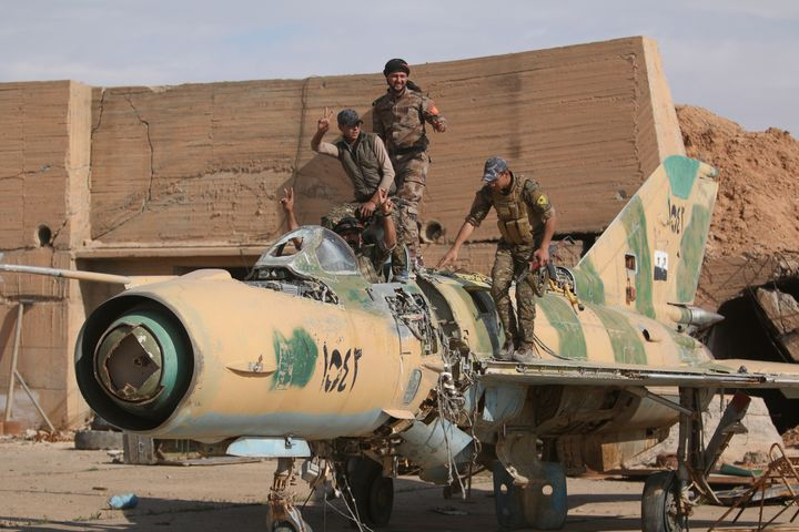 Fighters of the Syrian Democratic Forces pose on a damaged airplane inside Tabqa military airport after seizing it from
