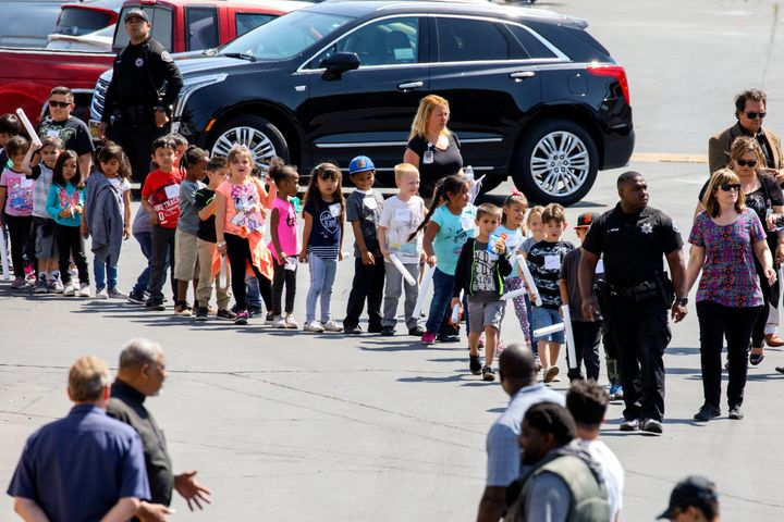 A police officer leads a line of children waiting to be reunited with their families after the shooting at their San Ber