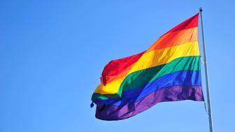 Rainbow flag over blue sky.